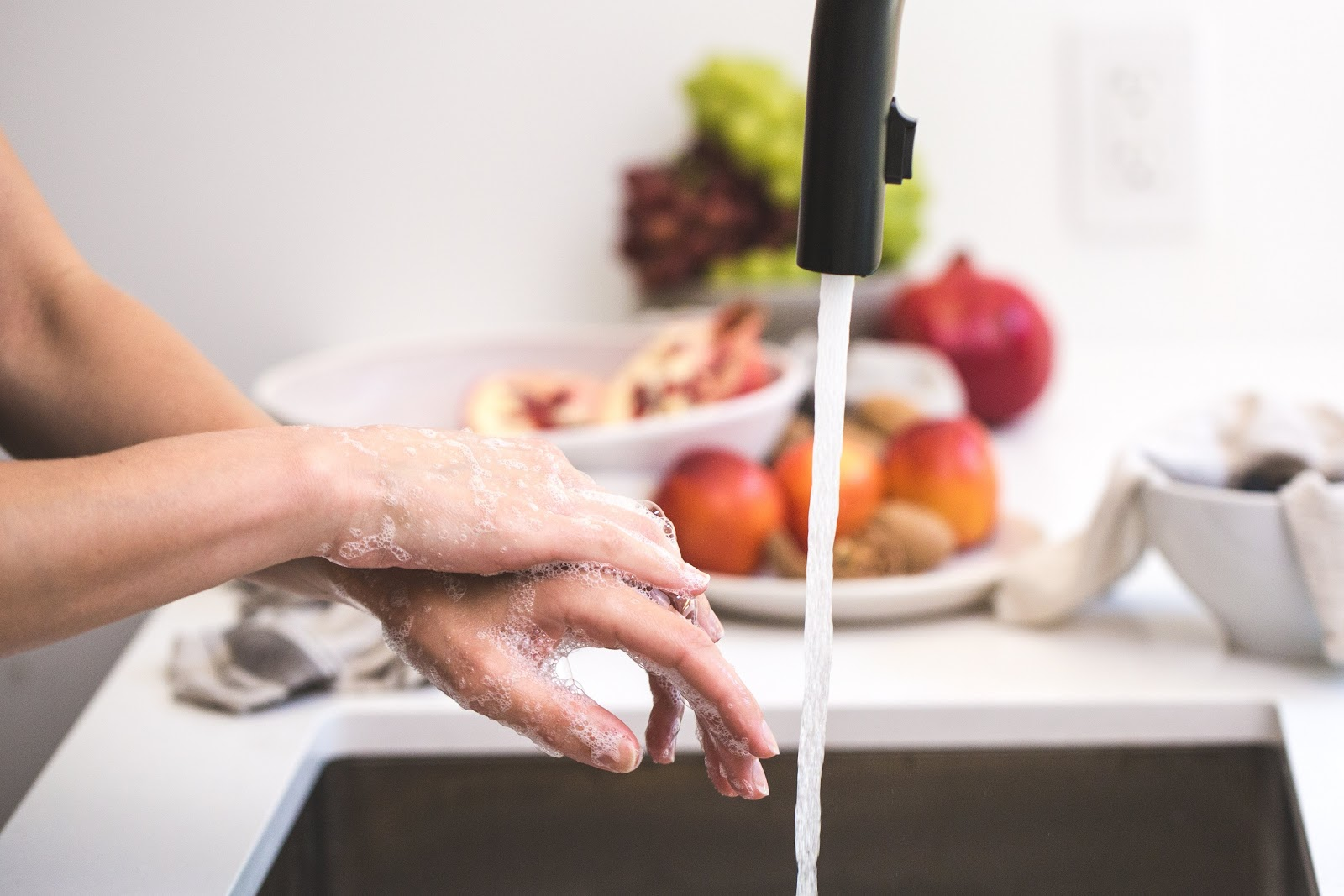 lathering hands under faucet running hard water