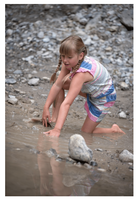 girl playing in dirty water