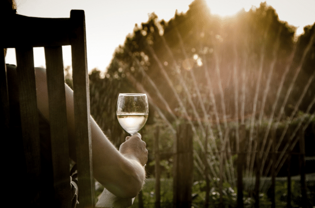 Person at home drinking wine with water sprinkler