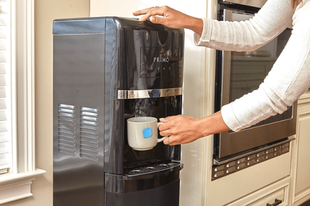 Woman pouring hot water into a tea cup with a Primo water dispenser